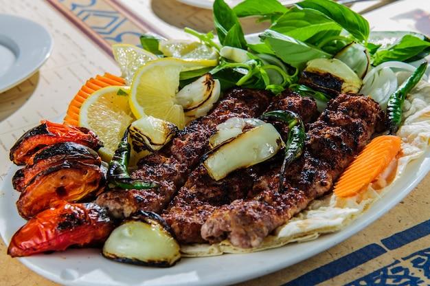 Bord van arabische oosterse barbecue, gemaakt van verschillende soorten vlees, ondersteund met groenten