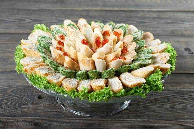 Bord vol heerlijke pannenkoekbroodjes met romige vulling en kaviaar versierd bovenop eten restaurant café koken keuken recept smakelijke honger portie schotel gastronomisch menu concept