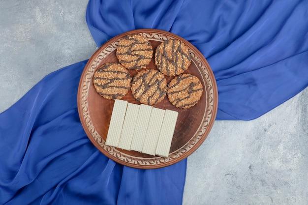 Bord vol koekjes met zaden en heerlijke wafels op steen.