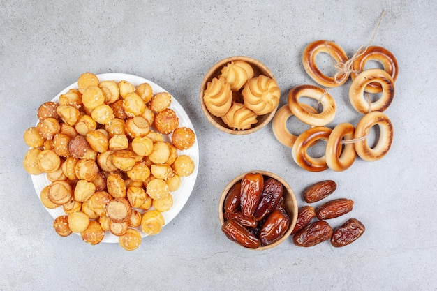 Bord vol koekjes naast kommen dadels, koekjes en gebonden sushki. hoge kwaliteit foto