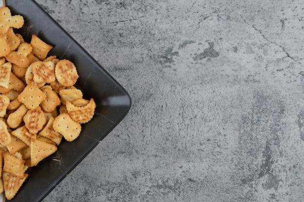 Bord vol met droge gezouten crackers op marmer.