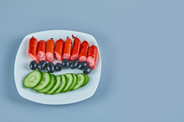 Bord worstjes olijven en plakjes komkommer op blauw on