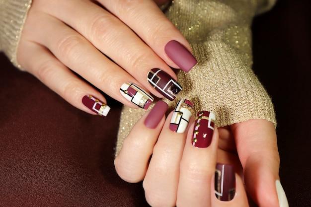 Bordeauxrood en wit ontwerp op lange nagels met gouden lijnen.