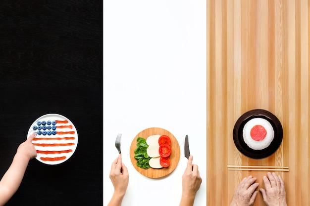 Borden met eten in de vorm van vlaggen van amerika, italië en japan.