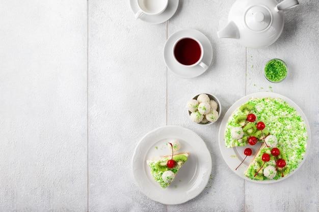 Borden met heerlijke cake raffaello met groene kokos vlokken en kopje thee op witte houten tafel