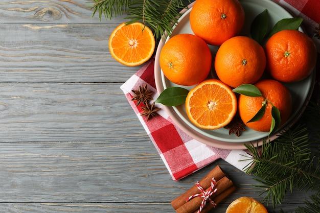 Borden met mandarijnen, dennentakken, servet en kaneel