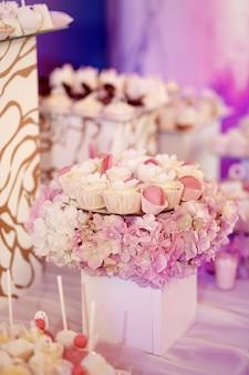 Borden met roze en witte snoepjes staan op blokjes met hortensia's