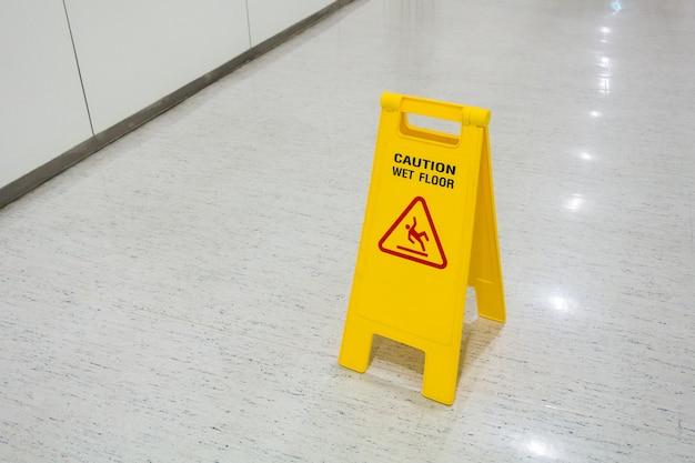 Borden plastic geel op de vloer tekst let op natte vloer in ziekenhuis