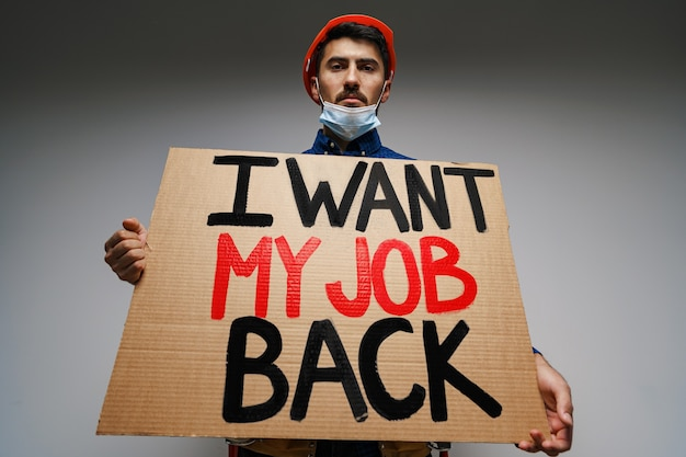 Bordje 'ik wil mijn baan terug' in handen van demonstrant met masker.