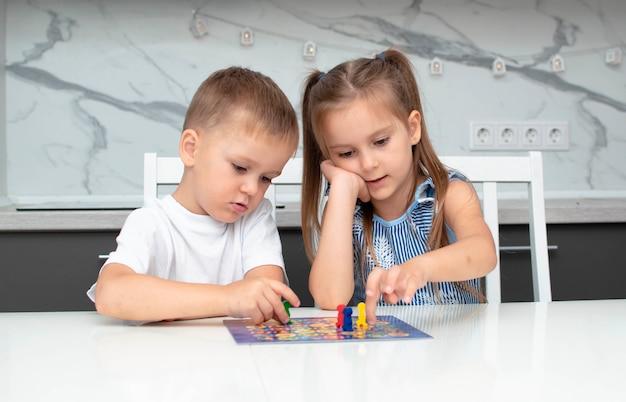 Bordspel en concept van vrijetijdsbesteding voor kinderen. kinderen hebben plezier, lachen en hebben plezier bij het spelen van bordspel. ze houden figuren in hun handen, rode, blauwe, groene fiches. jongen en meisje spelen thuis bordspel