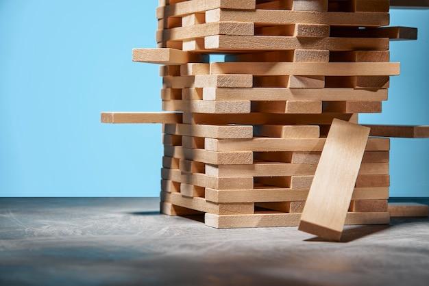 Bordspel jenga, een toren van houten blokken op blauw