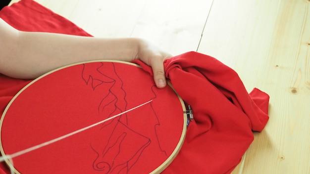 Borduur naaien met de hand van de vrouw ambachtelijk werk en vrouwelijke handen ambachtelijk werk met een draad naald naaien