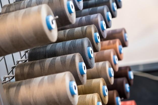 Borduurgarenklos gebruikt in de kledingindustrie, rij veelkleurige garenrollen.