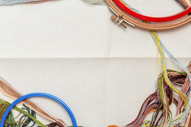 Borduurramen, borduurset met gekleurde draden en canvasachtergrond met kopieerruimte