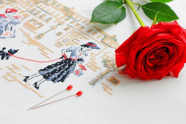 Borduurwerk met een afbeelding van een jonge vrouw op haar achtergrond rode roos en pinnen