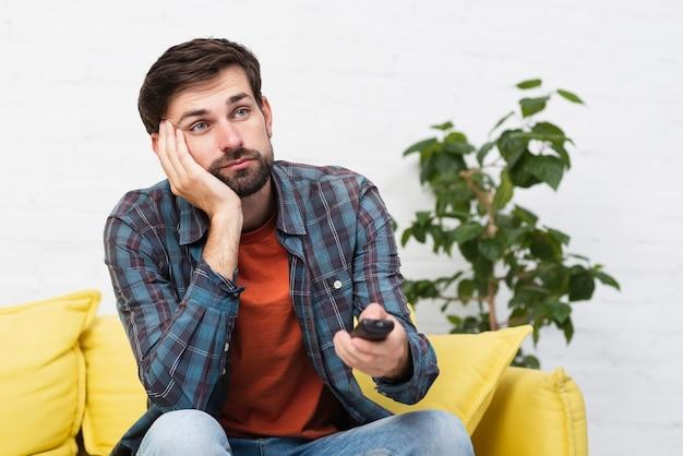 Bored jonge man met een afstandsbediening