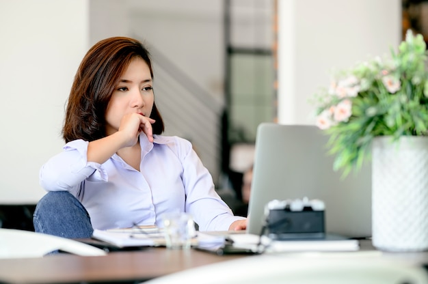 Bored jonge onderneemsterzitting bij bureau terwijl het werken met laptop.