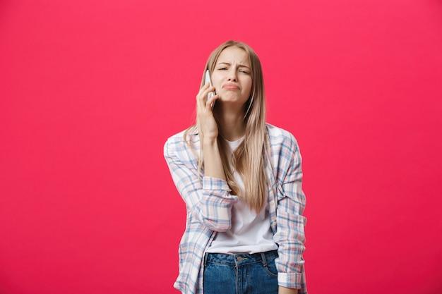 Bored meisje die de telefoon uitnodigen en gek op een roze achtergrond kijken