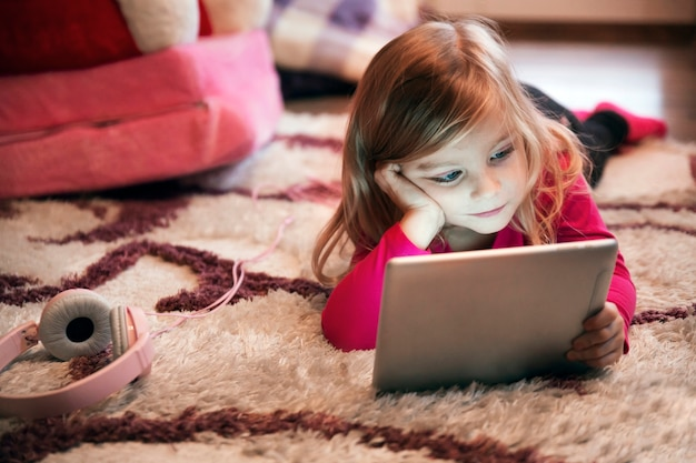 Bored meisje die tablet op tapijt gebruiken