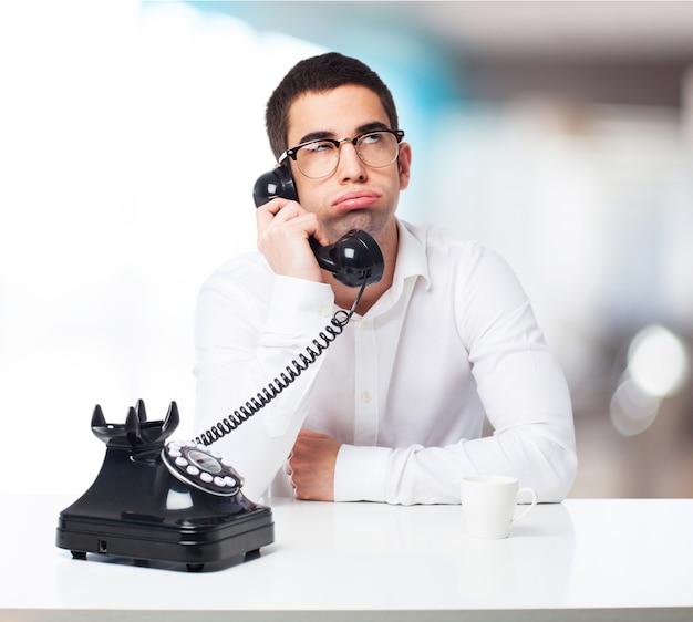 Bored mens die op een zwarte telefoon