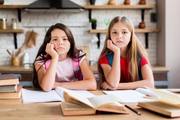 Bored multi-etnische schoolmeisjes die huiswerk doen