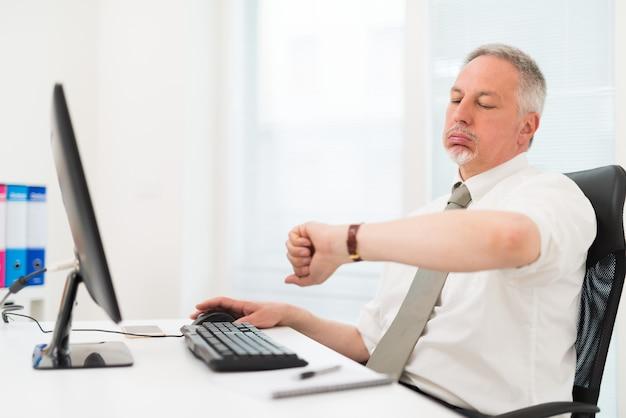 Bored zakenman die zijn horloge bekijkt