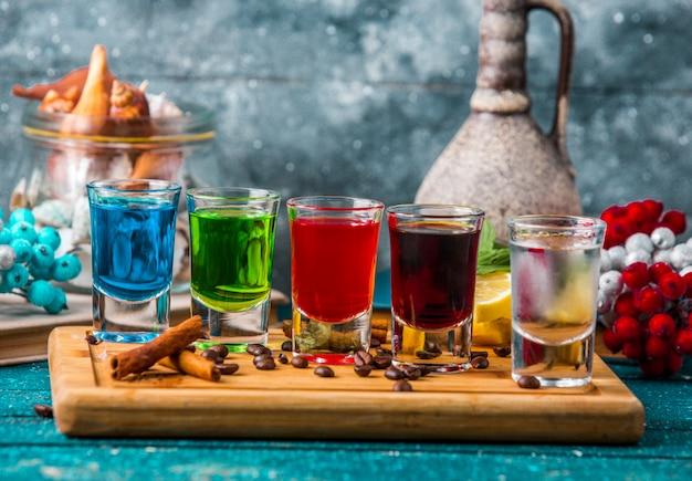 Borrelglaasjes met kleurrijke drankjes op een houten bord