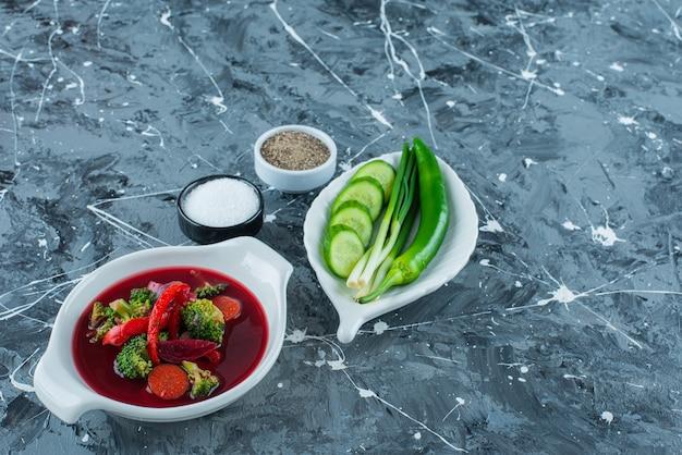 Borsch soep in een kom naast groenten en kruiden, op de blauwe achtergrond.