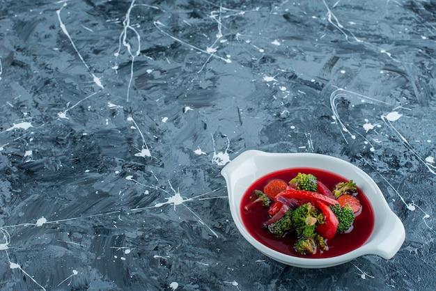 Borsch soep in een kom, op de blauwe achtergrond.