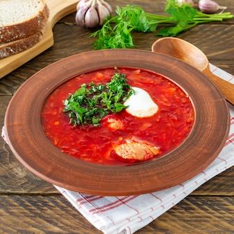 Borsch - traditionele oekraïense en russische bietensoep op donkere houten achtergrond. geserveerd met roggebrood, knoflook en zout.