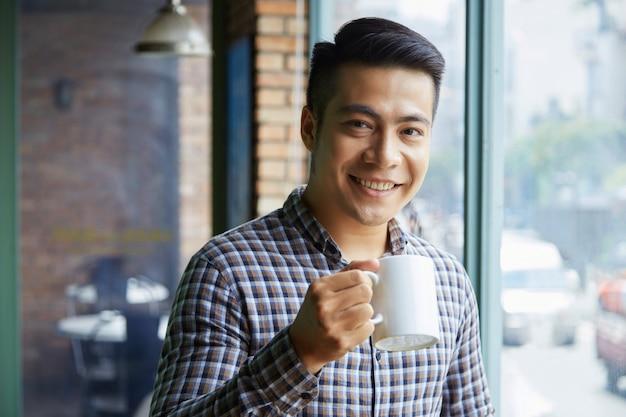 Borstbeeld van jonge aziatische kerel die thee in een koffie drinken
