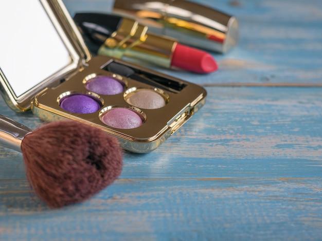Borstel de ingestelde oogschaduw en lippenstift op een blauwe vintage tafel.
