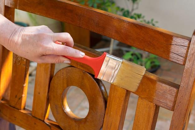 Borstel die planken en houten balken bedekt met eikenkleurige binnenvernis. doe het zelf. doe-het-zelf