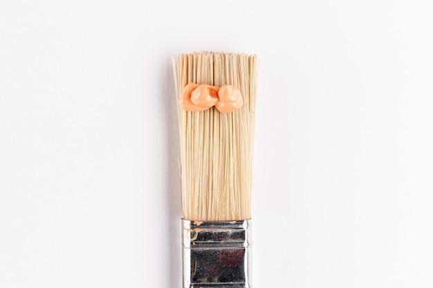Borstel met oranje verf en eenvoudige achtergrond
