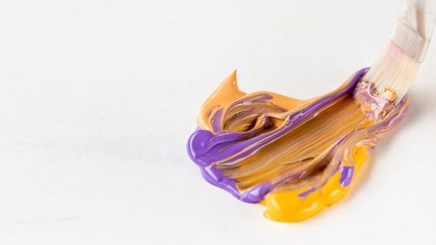 Borstel met paarse en oranje gemengde verf