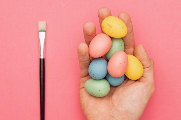 Borstel naast de hand met gekleurde eieren