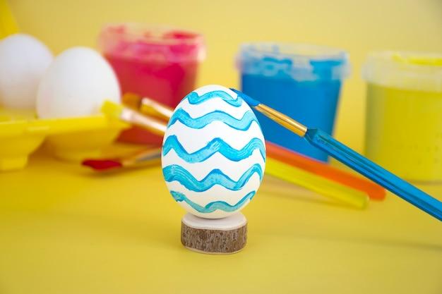 Borstel tekening decor op ei met eieren in geel eierrekje, kleurrijke verf en borstels op achtergrond.