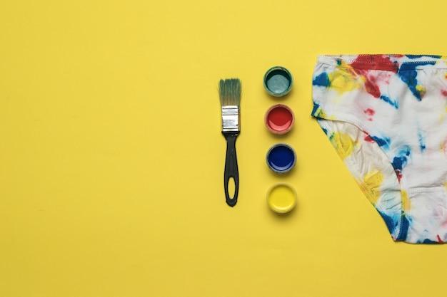 Borstel, verf in vier kleuren en een slipje in tie-dye-stijl op een gele achtergrond. gekleurd ondergoed in huis.