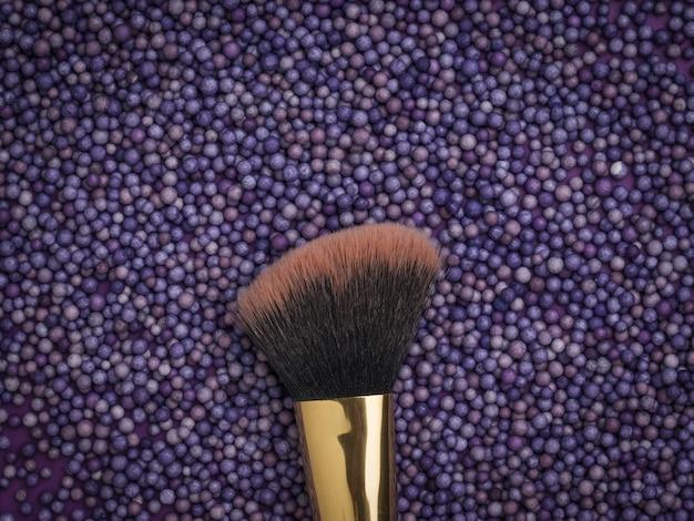 Borstel voor cosmetica over paarse ballen. gezichtsverzorging.