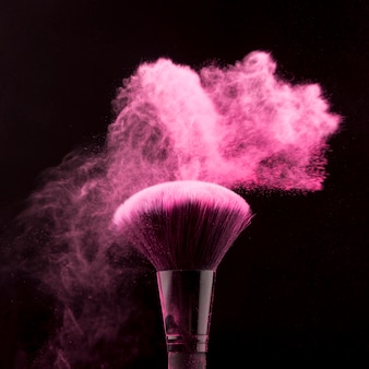 Borstel voor het aanbrengen van make-up in stof van poeder op een donkere achtergrond