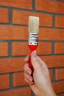 Borstel voor het schilderen van de muren in de meisjeshand op een muur van tegenoverliggende rode baksteen