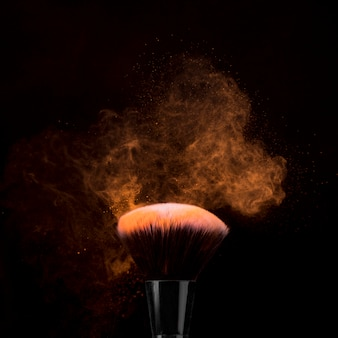 Borstel voor make-up in poeder burst op donkere achtergrond