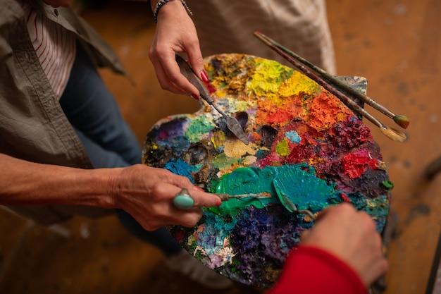 Borstels dichtbij palet. bovenaanzicht van drie vrouwelijke kunstenaars die hun penselen in de buurt van het kleurenpalet houden