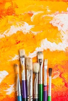 Borstels die bij het oranje schilderen liggen