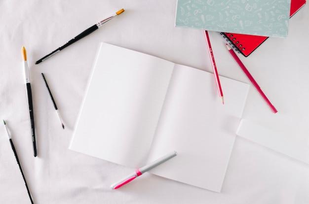 Borstels en potloden rond geopend notitieboekje