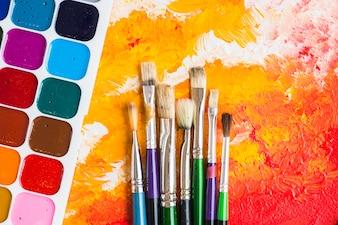 Borstels in de buurt van aquarel op schilderij