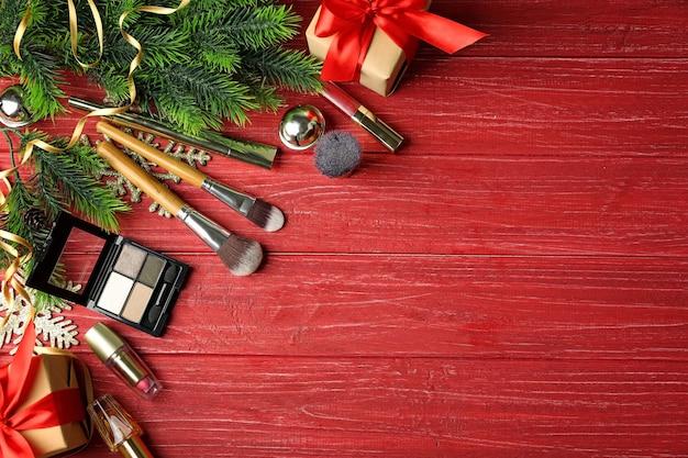 Borstels met kleurrijke make-upcosmetica en ingepakte geschenken op rood houten oppervlak