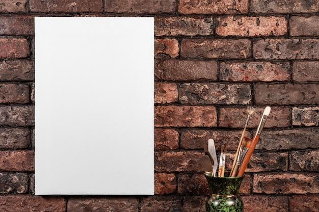 Borstels palet en wit canvas op een rode bakstenen muur achtergrond