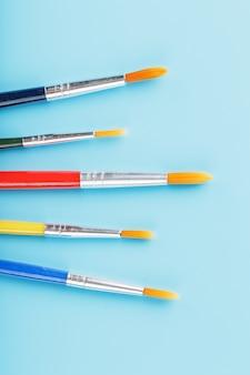 Borstels van verschillende kleuren voor tekenen, creativiteit en kunst op een blauwe achtergrond.