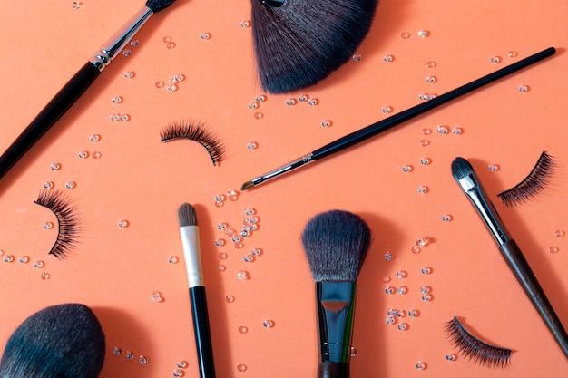 Borstels voor make-up van verschillende groottes op een pasteloranje